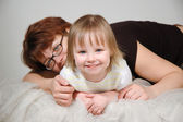 Young mother embraces the young daughter and smile — Stock Photo