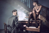 Sexy couple in an intimate situation with piano — Stock Photo