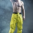 Muscular man in a fashion pose in snowboard trausers — Stock Photo