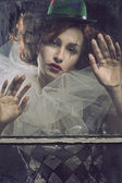 Sad Pierrot woman behind the glass — Stock Photo