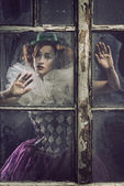 A lonely pierrot woman behind the glass — Stock Photo