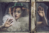 A lonely sad pierrot woman behind the glass — Stock Photo