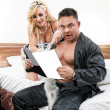 Young sexy couple reading together a magazine in their bedroom - Stock Photo
