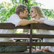 Stock Photo: Kissing couple on the bench