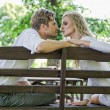 Kissing couple on the bench — Stock Photo