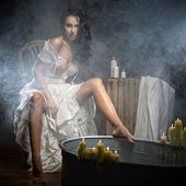 Woman relaxing in bath with candels — Stock Photo
