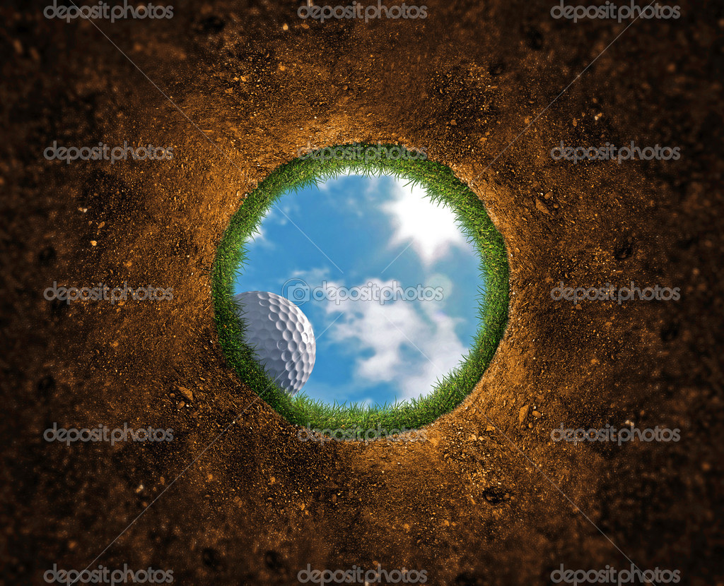 Golf ball falling over the edge into the hole  Stockfoto #8536308