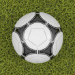 Soccer ball on a grass field background — Photo