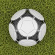 Soccer ball on a grass field background — Stok fotoğraf