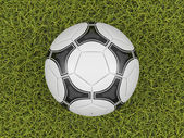 Soccer ball on a grass field background — Stock Photo