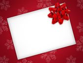 Christmas card with red ribbon on a red background — Stock Photo