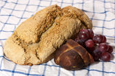 Fresh organic bread with cold meat and grapes — Stock Photo
