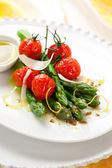 Green asparagus with roasted tomatoes — Stock Photo