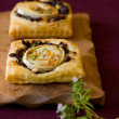 Royalty-Free Stock Photo: Puff pastry goat\'s cheese and red  onion small tarts