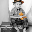 A boy with a teddy bear sitting on a suitcase. - Stock Photo