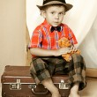 A boy with a teddy bear sitting on a suitcase. — Stock Photo