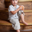 A cute boy with an orange in his hand sitting on the steps. — Stock Photo