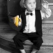 Cute little boy with a banana in his hand sitting on the steps. — Stock Photo #10050955