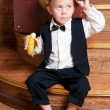 Cute little boy with a banana in his hand sitting on the steps. — Lizenzfreies Foto