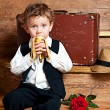 Cute little boy with a banana in his hand sitting on the steps. — Stock Photo