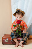 Cute little boy with the flower sitting on an old suitcase. He i — Stock Photo