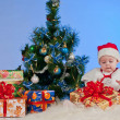 Royalty-Free Stock Photo: Charming baby (girl) in Santa Claus suit, sitting beside a Christmas tree d