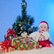 Charming baby (girl) in Santa Claus suit, sitting beside a Christmas tree d — Stock Photo
