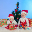 Foto Stock: Two cute babies (girl and boy) dressed as Santa Claus. Children are near gi