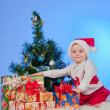 Funny  laughing  baby in Santa suit with a present box. — Stock Photo