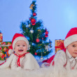 Two cute babies (girl and boy) dressed as Santa Claus. Children are near gi — Stock Photo #8135833