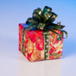 New Year's gift in festive packaging. Red box with green ribbon. — Stock Photo #8136182