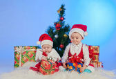 Two cute babies (girl and boy) dressed as Santa Claus. Children are near gi — Stock Photo