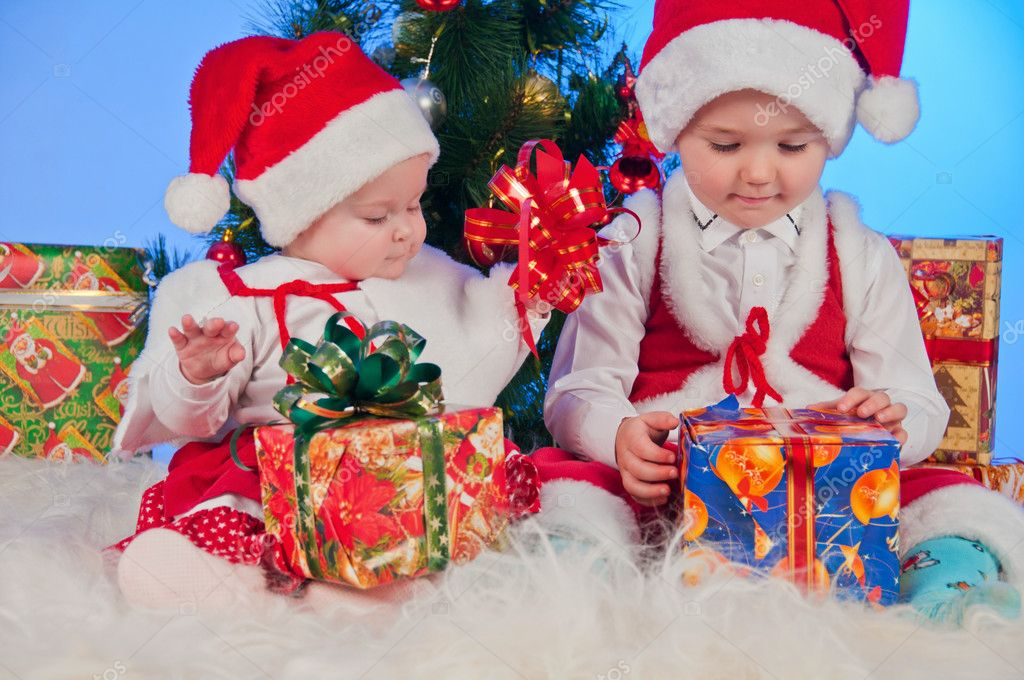 Two cute babies (girl and boy) dressed as Santa Claus. Children are near gifts and Christmas tree. — Stock Photo #8135826