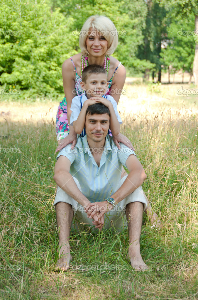 Portrait of happy family lying down on grass. — Stock Photo #9469610