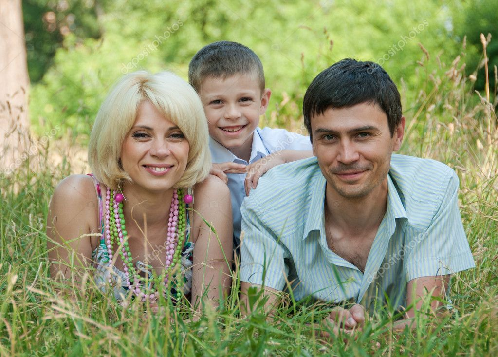 Portrait of happy family lying down on grass.  Stock Photo #9469621
