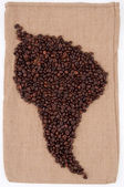 Coffee beans are laid out on the bag in the shape of South Ameri — Zdjęcie stockowe