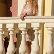 Stock Photo: A beautiful young blond sexy woman standing near the railing.
