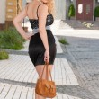 A beautiful young blond sexy woman with a bag in his hands. — Stock Photo