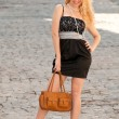 A beautiful young blond sexy woman with a bag in his hands. — Stock Photo #9652898