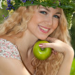 A beautiful blonde young woman with a wreath on his head eating — Stock Photo #9652953
