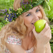 A beautiful blonde young woman with a wreath on his head eating — Stock Photo