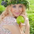A beautiful blonde young woman with a wreath on his head eating — Stock Photo #9652994