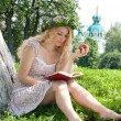Beautiful young blonde woman reading a book on the green backgro — Stock Photo #9653004