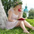 Beautiful young blonde woman reading a book on the green backgro — Stock Photo