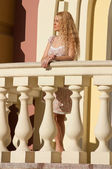 A beautiful young blond sexy woman standing near the railing. — Stock Photo