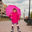 A girl on roller skates with an umbrella coming down the road. — Stock Photo