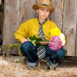 A boy with a bouquet of chrysanthemums against a wooden fence. — Stock Photo