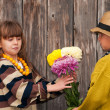 Stock Photo: Boy gives girl flowers. First love.