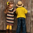 Stock Photo: Boy with girl peep over fence. Photos in old style.