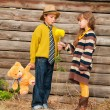 The boy with the girl standing near a wooden fence. — Stock Photo